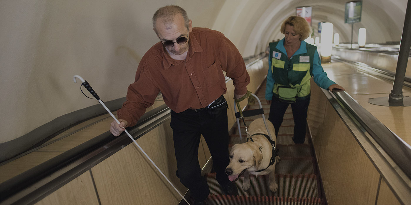 Visually impaired gentleman on escalator with guide dog