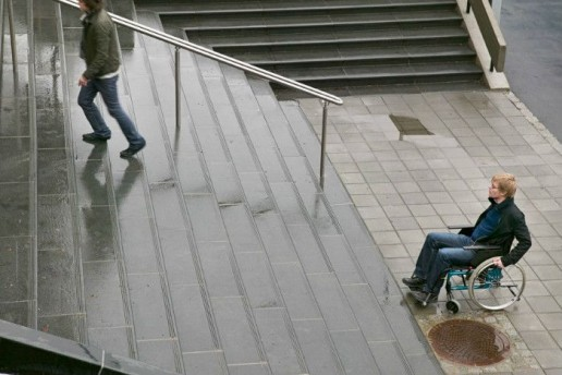 man in a wheelchair at the bottom of some steps