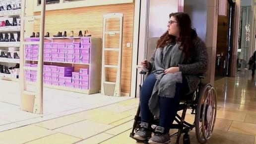 girl in a wheelchair looking in a shop window