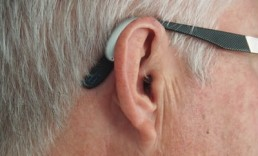 A man's ear with a hearing aid and glasses